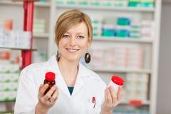 Женский аптекарь держа бутылки пилюльки в фармации Стоковая Фотография