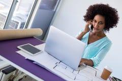 Женский архитектор говоря на мобильном телефоне пока работающ над компьтер-книжкой Стоковые Фото