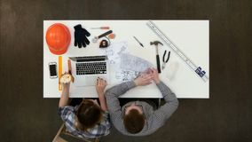 Женский архитектор обсуждая рисовать с ее сотрудником пока ел обед и печатать стоковое изображение