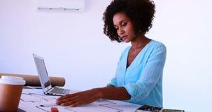 Женский архитектор работая на светокопии над чертя таблицей 4k видеоматериал