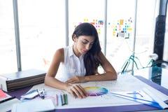 Женский архитектор работая на светокопии на ее столе Стоковые Фотографии RF