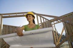 Женский архитектор смотря отсутствующий пока держащ светокопию Стоковое Изображение