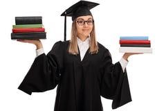 Женский аспирант держа 2 стога книг Стоковые Фото