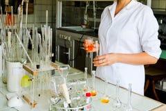 Женский ассистент лаборатории, доктор, химик, работы с склянками, пробирками, делает решения, медицины, ингридиенты смешиваний стоковая фотография