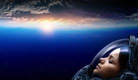 Женский астронавт в космосе на орбите планеты стоковая фотография