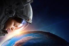 Женский астронавт в космосе на орбите планеты стоковые изображения