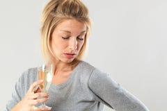 Женский алкоголизм для молодой белокурой женщины держа шипучее напитк вино Стоковые Фотографии RF