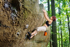 Женский альпинист взбираясь без веревочки на скалистой стене Стоковое Изображение