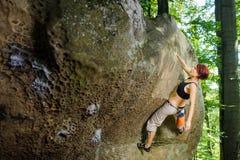 Женский альпинист взбираясь без веревочки на скалистой стене Стоковое Фото