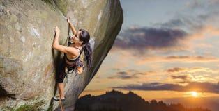 Женский альпинист взбираясь большой валун в природе с веревочкой Стоковое Изображение RF