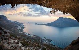 Женский альпинист утеса на заходе солнца Стоковое Изображение RF
