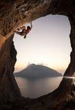 Женский альпинист утеса на заходе солнца, Kalymnos, Греция Стоковое Фото