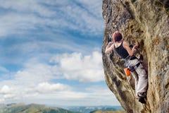 Женский альпинист утеса на крутой свисая скале утеса Стоковые Фото