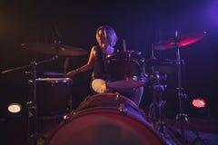 Женский барабанщик играя набор барабанчика в загоренном ночном клубе Стоковые Фото
