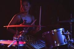 Женский барабанщик играя набор барабанчика в ночном клубе Стоковая Фотография RF