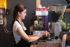 Женский бармен делает кофе используя машину кофе Стоковая Фотография