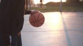 Женский баскетболист баскетбола отскакивая шарик Замедленное движение сняло тренировки баскетболиста на outdoors видеоматериал