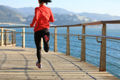 Женский бегун бежать на променаде взморья Стоковые Изображения