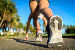 Женский бегун готовый для спринта Стоковая Фотография