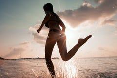 Женский бегун на пляже на силуэте захода солнца в воздухе более далеко Стоковое фото RF