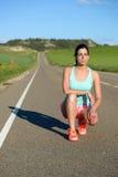 Женский бегун отдыхая на тренировке дороги стоковое фото rf