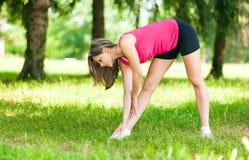 Женский бегун протягивая перед ее разминкой стоковые фотографии rf