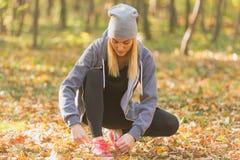 Женский бегун связывая ее ботинки и подготавливая для бега снаружи стоковые фото