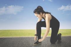 Женский бегун связывая шнурки ботинка Стоковые Фотографии RF