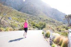 Женский бегун с предпосылкой горы Стоковые Фото