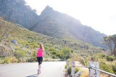 Женский бегун с предпосылкой горы Стоковое фото RF