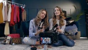 Женский блоггер моды 2 демонстрируя ботинки тенденции для делать видео- блог о стиле моды видеоматериал