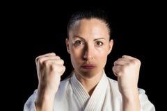 Женский боец выполняя позицию карате Стоковые Фото