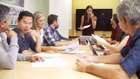Женский босс адресуя встречу вокруг таблицы зала заседаний правления видеоматериал