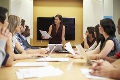 Женский босс адресуя встречу вокруг таблицы зала заседаний правления стоковые изображения