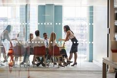 Женский босс стоит склонность на таблице на деловой встрече стоковое изображение rf