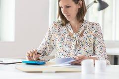Женский бухгалтер делая вычисление на голубом ручном calculato Стоковая Фотография RF