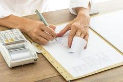 Женский бухгалтер высчитывая и рассматривая номера на получении Стоковые Изображения
