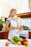 Женский варить в кухне Стоковое Изображение
