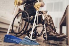 Женский ветеран в кресло-коляске убирает дом стоковые изображения