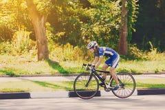 Женский велосипедист едет велосипед гонок на дороге Стоковые Изображения