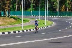 Женский велосипедист едет велосипед гонок на дороге Стоковое Фото