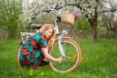 Женский велосипедист с винтажным белым садом велосипеда весной Стоковые Изображения RF