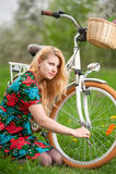 Женский велосипедист с винтажным белым садом велосипеда весной Стоковое Изображение