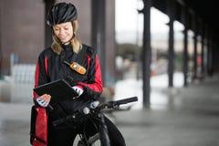 Женский велосипедист с сумкой курьера используя цифров Стоковое фото RF
