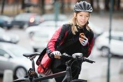 Женский велосипедист с сумкой курьера используя Стоковое Фото