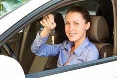 Женский водитель показывая ключ автомобиля стоковые фото