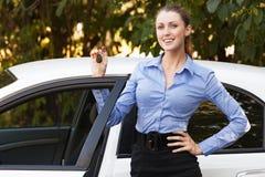 Женский водитель показывая ключ автомобиля стоковое фото rf