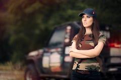 Женский водитель в обмундировании армии рядом с автомобилем дороги Стоковые Изображения RF