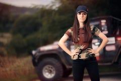 Женский водитель в обмундировании армии рядом с автомобилем дороги Стоковые Фото