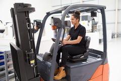 Женский водитель платформы грузоподъемника работая в фабрике Стоковые Фотографии RF